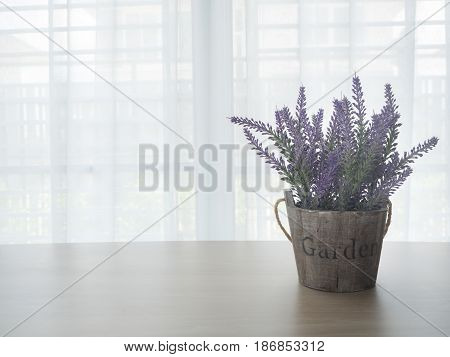 wood table with left free space and purple lavender flowerpot on beautiful white drape window texture background at living room.