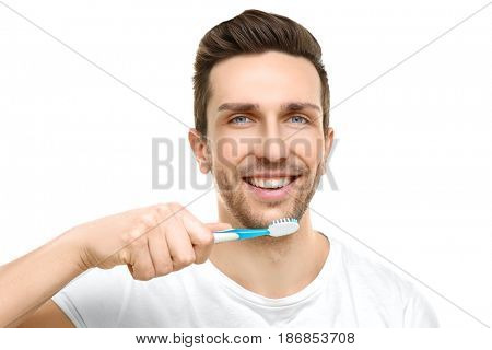 Young handsome man brushing teeth on white background