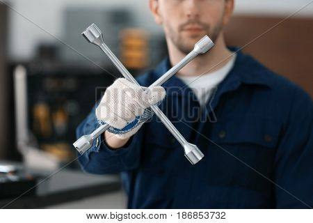 Auto mechanic with wheel wrench in car repair shop