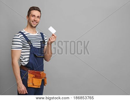 Handsome worker with business card on grey background