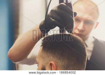 Man getting haircut with trimmer by hairstylist at barbershop. Modern hair salon
