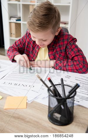 Naughty Young Boy Drawing On Father's Business Papers At Office