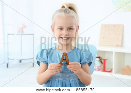 Cute little girl with letter A at home