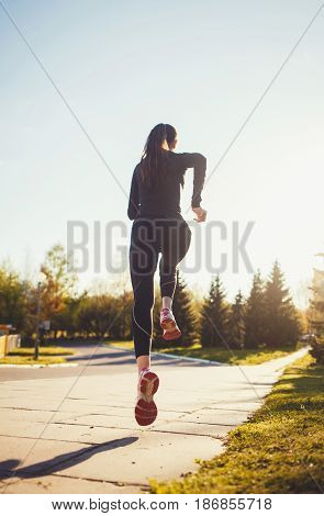 Runner athlete running in park. woman fitness jogging workout wellness concept.