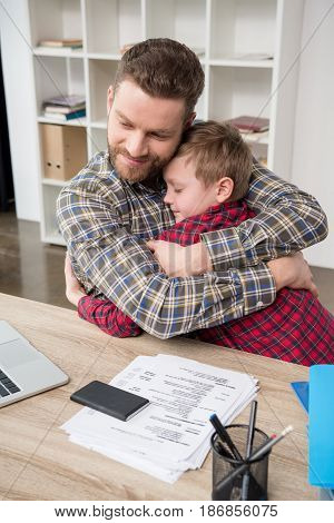 Father Businessman Hugs His Son At Home Office