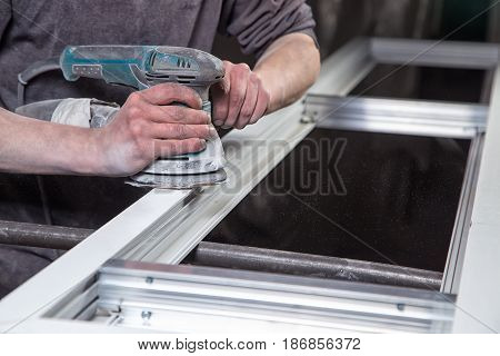 Hard worker grinding metal doors in workshop