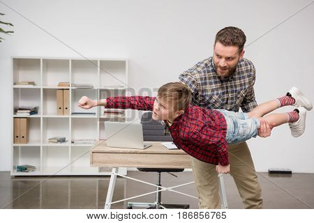 Man Freelancer Having Fun With Son At Home Office