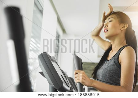 Asian woman with sweat exercising on Elliptical trainer machine at the gym.