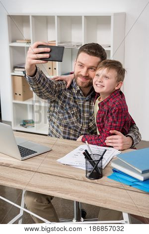 Businessman Freelancer Taking Self Portrait With Son At Home Office