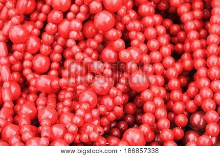 Red wooden beads as stylish red embossed background with painted wood texture