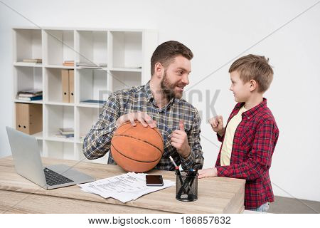 Businessman Freelancer With His Son Wit Ball At Home Office