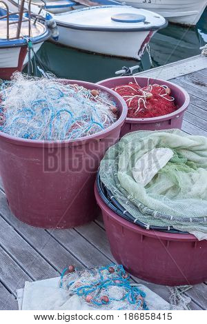 fishing nets and tackles in containers on the pier