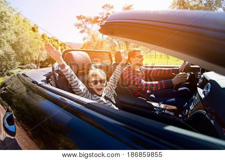 excited family of two young father and his smiling son with hands high up in the air enjoying road trip in convertible car journey and vacation concept sun flare