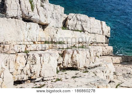 Beautiful white rock ocean coast as geology stone layers going in to the blue sea as background full of bright sunlight on a sunny summer day