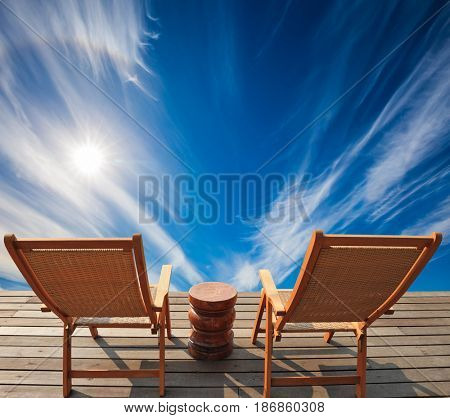 Lovely place to relax. Two deck chairs on a wooden platform. Cirrus clouds in the autumn sky.  The concept of recreational tourism