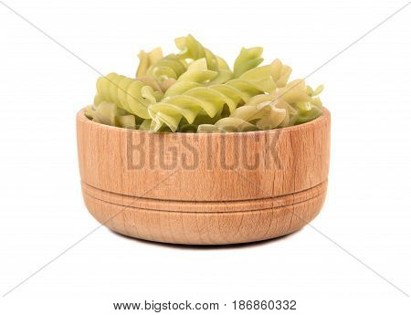 Green pasta fusilli in a small bowl on a white background