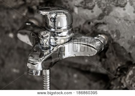 Beauty of shiny new metal chrome surface on a bathroom tap with water drops on it and concrete wall background as modern interior design background