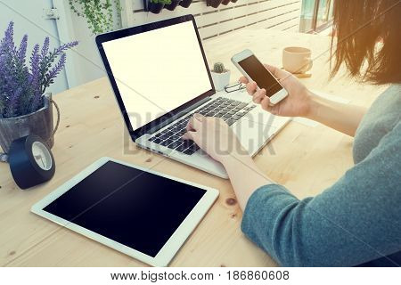 office table with young working woman is hand hold smartphone tablet cell phone and using laptop purple lavender flower at home office. concept of job search online. view form rear office table.
