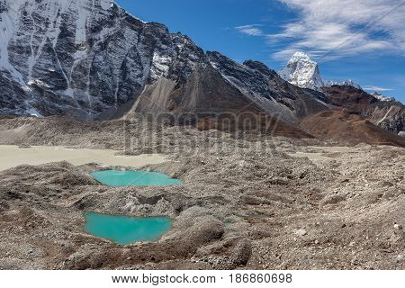 Two Small Moraine Lakes Of Turquoise Color And Snowy Mountain Peaks On The Horizon. Bright Blue Mora