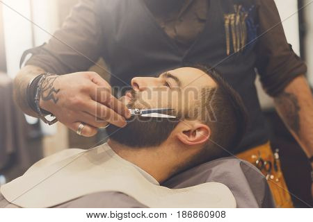 Barber make beard haircut with scissors in barbershop, closeup of client's head. Hairstyle in male hair salon