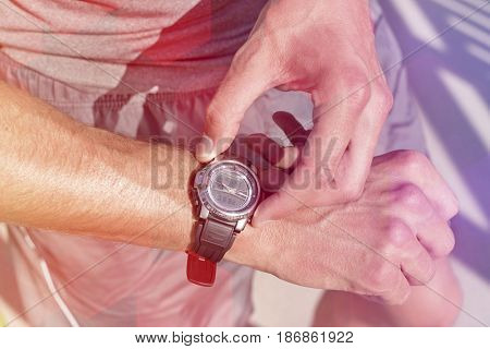 Midsection of fit man checking time on path in park