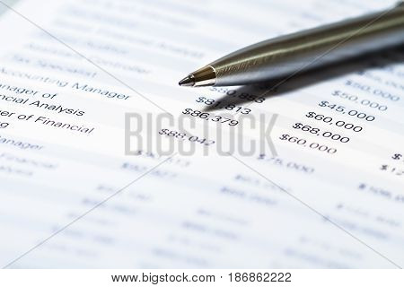Finance focus data number pen reviewing financial figures
