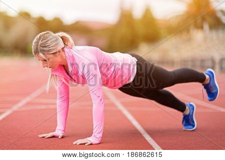 side view of young slim attractive woman doing plank exercise at outdoor stadium core training and fitness concept sun flare