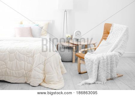 Chair near comfortable bed with soft beige coverlet and pillows in light modern room
