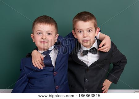 two friends, elementary school boy near blank chalkboard background, dressed in classic black suit, group pupil, education concept