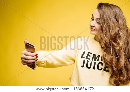 Stylish smiling beautiful brunette woman in yellow sweatshirt, posing and making self portrait at call phone. Fashionable girl with long hair, makeup, perfect manicure using call phone, taking photo.