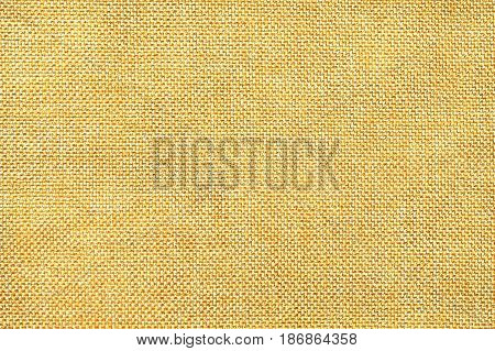 Light yellow and white background of dense woven bagging fabric closeup. Structure of the golden cloth with natural texture. Cloth backdrop.