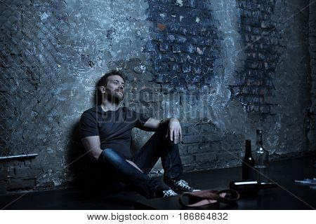 Enjoying my own reality. Puzzled obsessed scruffy man sitting in the darkness while being stoned and expressing frustration