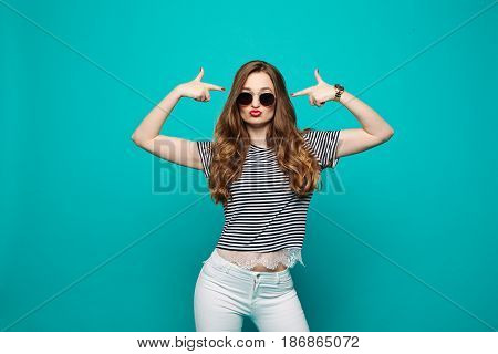 Swag and stylish hipster girl with red lips, wearing in sunglasses, making duck face, sending kiss and gesturing, pointing by hands like guns near head. Fashionable beautiful brunette posing at blue studio.