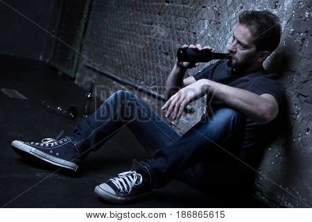 Realizing my useless life. Reckless mature inaccurate man sitting on the floor in the darkness while holding bottle and drinking alcohol