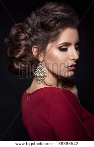 Beautiful woman with stylish haircut and big earrings looking down over shoulder, touching neck by hand. Brunette girl posing in dark studio, wearing red dress, with evening make up and long eyelashes