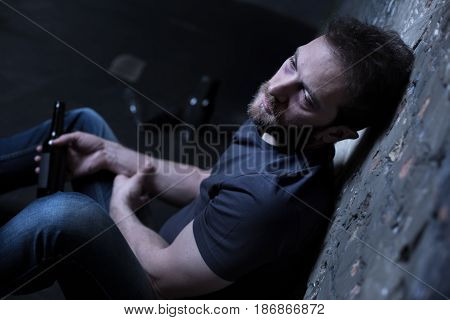 Apathy of my soul. Depressed reckless hopeless man sitting on the floor in the basement while expressing sadness and drinking alcohol