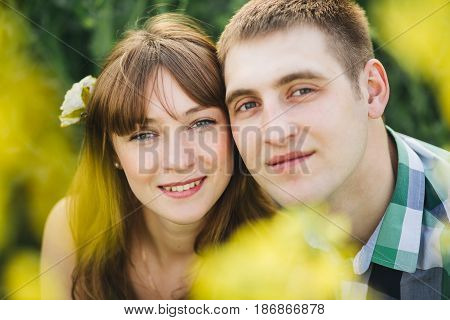 Portrait of couple of young boyfriend and girlfriend smiling at camera. Couple among flowers, touching by face each other. Brunette with flower in long hair wearing dress, man in checked shirt.