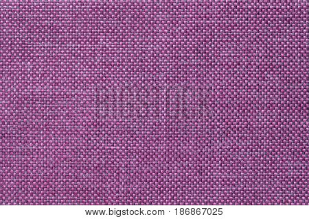 Dark violet woolen background of dense woven bagging fabric closeup. Structure of the purple cloth with natural texture. Cloth backdrop.