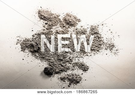 Word new written in grey ash dust dirt as a irony oxymoron paradox concept for old news business sale death life future advertisement background