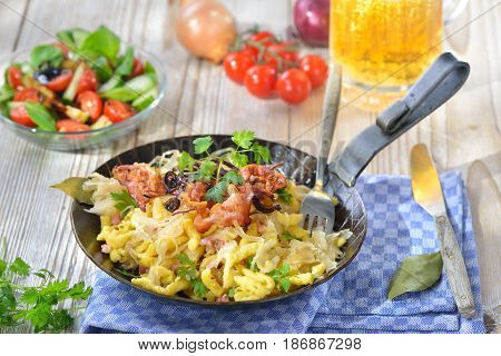 Swabian spaetzle with sauerkraut, fried bacon and onion rings on a wooden table with a Munich beer and a side salad