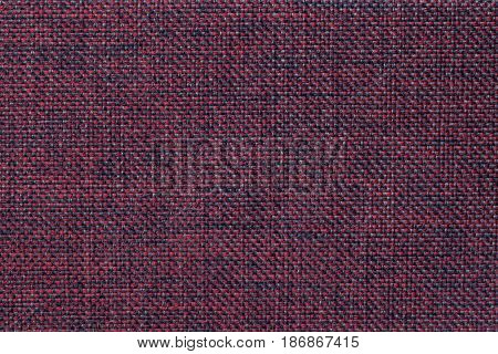 Dark red and black woolen background of dense woven bagging fabric closeup. Structure of the purple cloth with natural texture. Cloth backdrop.