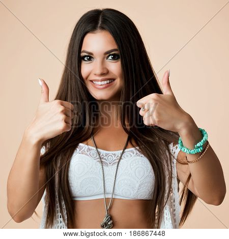 Studio portrait of stylish pretty positive brunette girl showing gesture if good and super by big fingers. Toothy smiling and looking at camera. Wearing white top and knit cardigan