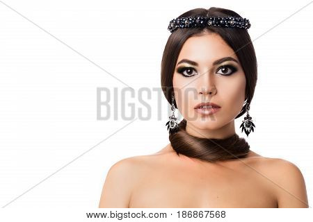 Portrait of beautiful brunette woman with big earring and shinny accessories. With hair around neck, perfect arabic makeup. Looking at camera. Isolate shot on white background. Front view.