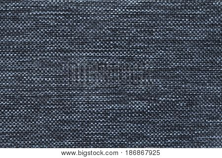 Navy blue shiny background of dense woven bagging fabric closeup. Structure of the denim cloth with natural texture. Cloth backdrop.