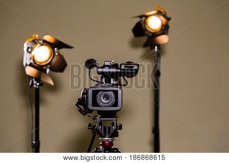 Video camera (camcorder) on a tripod and two halogen spotlights with Fresnel lenses. Shooting an interview.