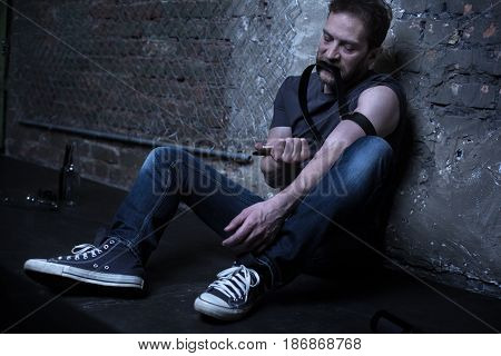 Having serious problems with my health . Scary homeless addicted man sitting on the floor while using rubber band and making drug injection