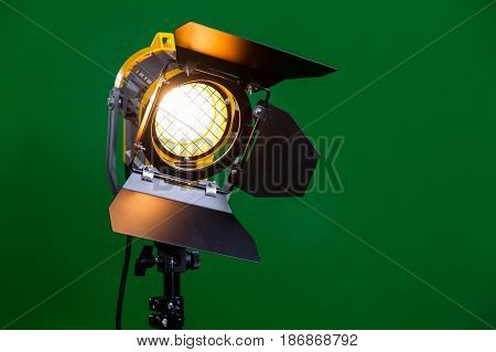 Halogen spotlight with a Fresnel lens on green background close-up.