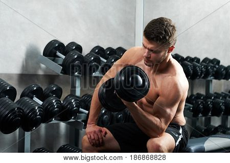 Handsome young shirtless fitness man lifting dumbbells weight training at the gym copyspace workout exercising weightlifting bodybuilding athletics physical effort energy concept.