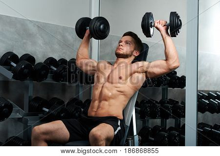 Young male bodybuilder doing weightlifting at the gym using heavy dumbbells copyspace athletics sports sportsman people lifestyle fitness energy activity concept.