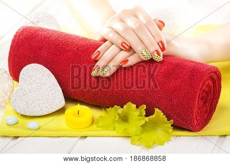 Luxury red manicure with oil and candles, and towel on the white wooden table.